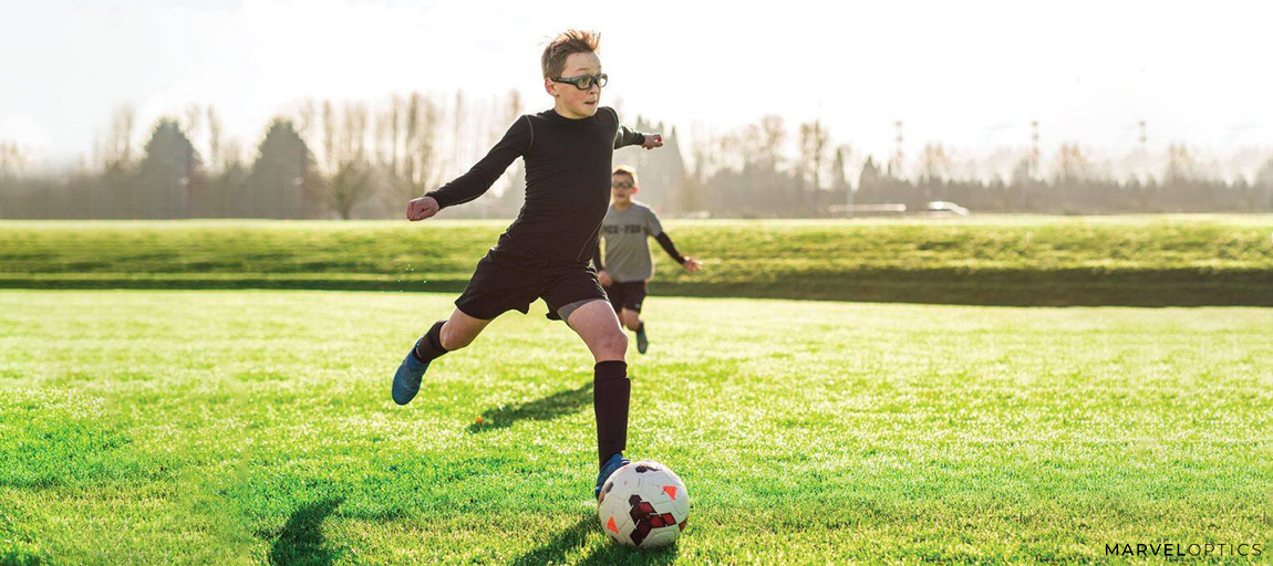 boy with glasses field running