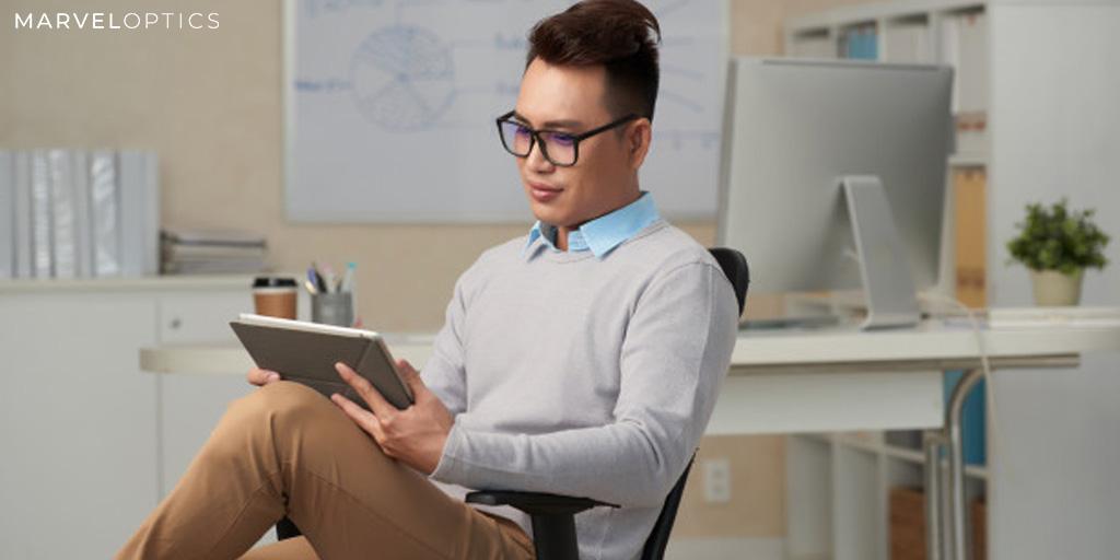 man wearing anti blue light glasses on his laptop