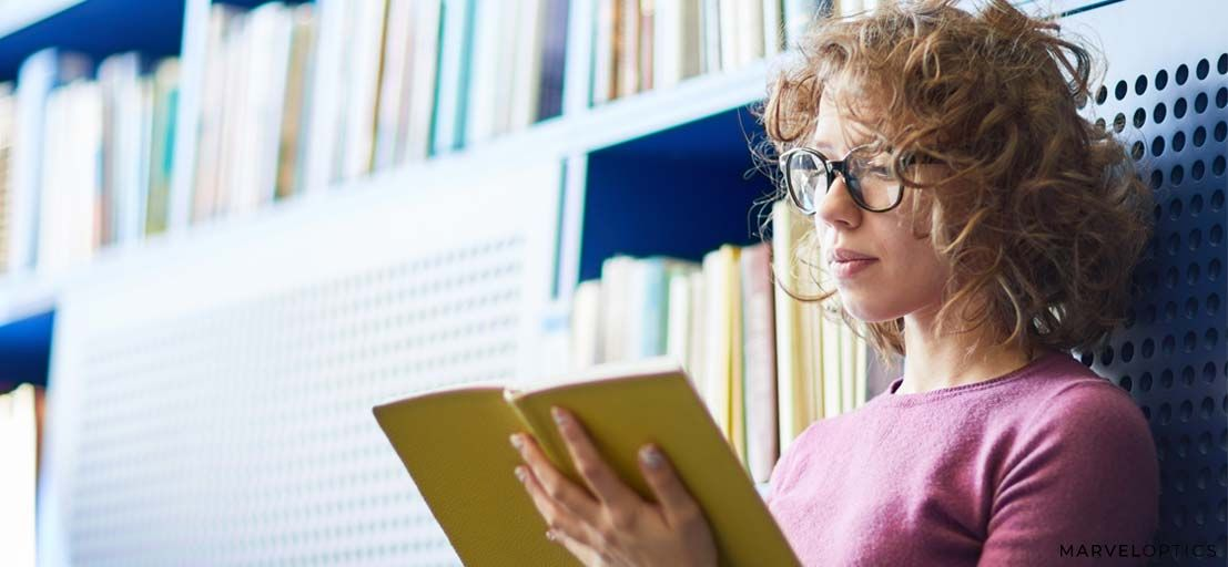 woman wearing prescription glasses while reading